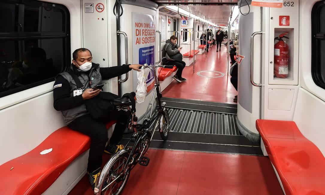 Homem usando uma máscara respiratória viaja sozinho em vagão no metrô de Milão, na Itália Foto: Miguel Medina / AFP