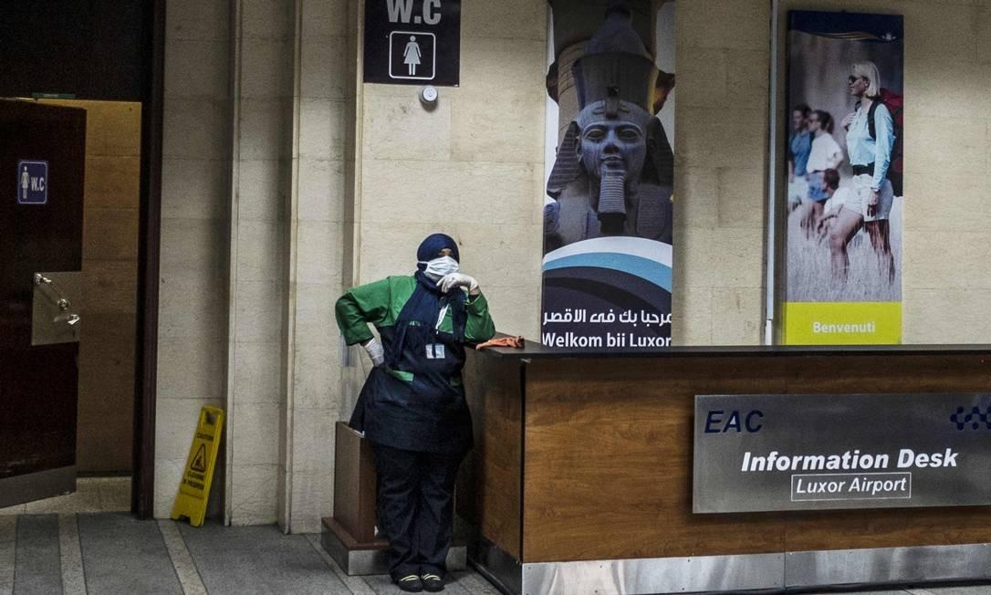Trabalhador egípcio usa uma máscara protetora no balcão de informações do saguão de desembarque do aeroporto de Luxor, no alto Egito, na cidade antiga, onde 45 casos suspeitos de doença por coronavírus Covid-19 foram detectados Foto: Khaled Desouki / AFP