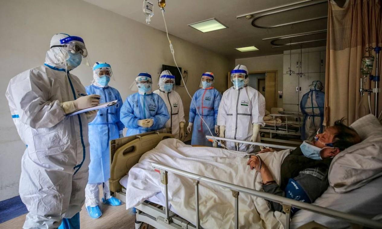 Equipe médica fala com paciente infectado pelo coronavírus no Hospital da Cruz Vermelha em Wuhan, na província central de Hubei, na China, considerado o epicentro da epidemia mundial Foto: STR / AFP