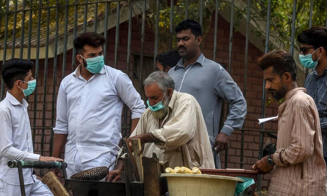 Clientes, usando máscara de proteção, compram milho de ambulante em rua de Karachi, no sul do Paquistão Foto: Asif Hassan / AFP