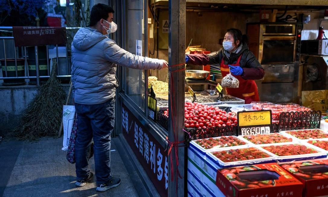 Cliente e freirante usam máscaras de proteção em Pequim, China Foto: Greg Baker / AFP