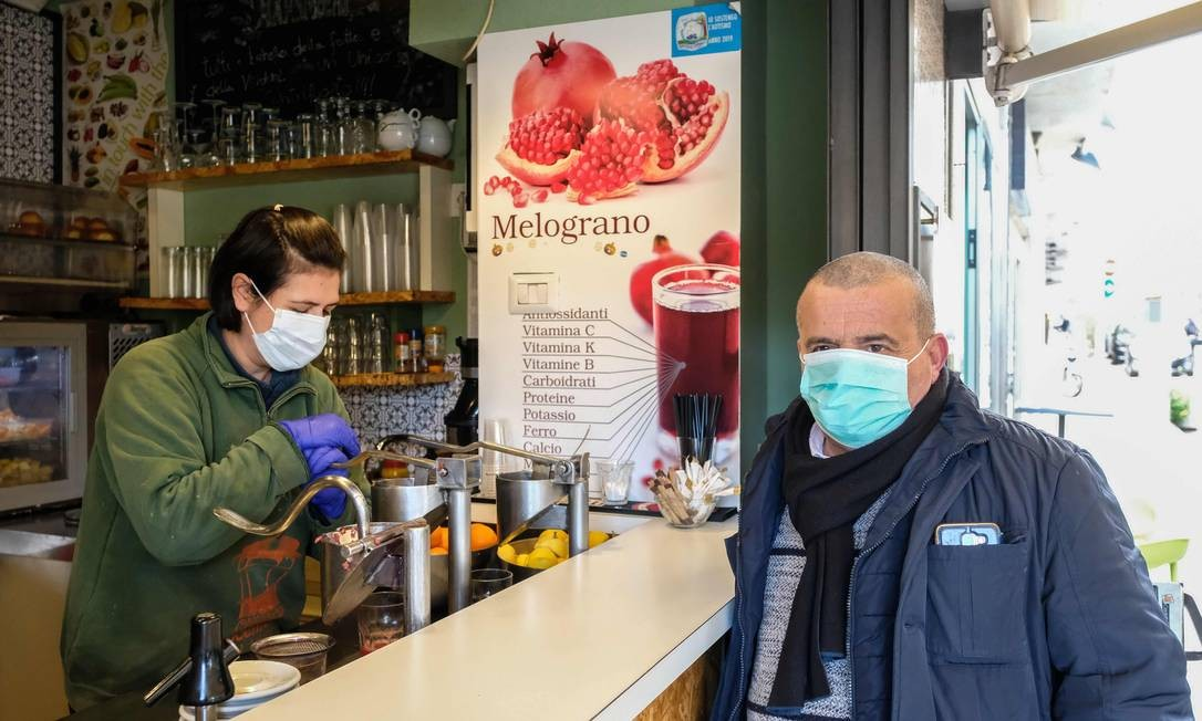 Homem usando máscara respiratória espera por garçonete que também usa uma máscara um balcão de café em Messina, na Sicília, Itália, onde 60 milhões de pessoas estão sofrendo medidas restritivas do governo para tentar conter a expansão do novo coronavírus Foto: Giovanni Isolino / AFP