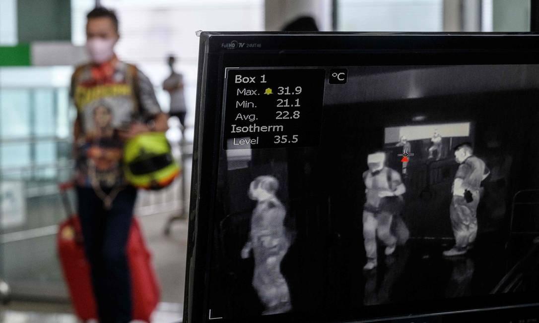 Passageiro usa marca facial ao passar pela triagem térmica ao entrar no Aeroporto Internacional Chek Lap Kok de Hong Kong, nesta terça Foto: Anthony Wallace / AFP