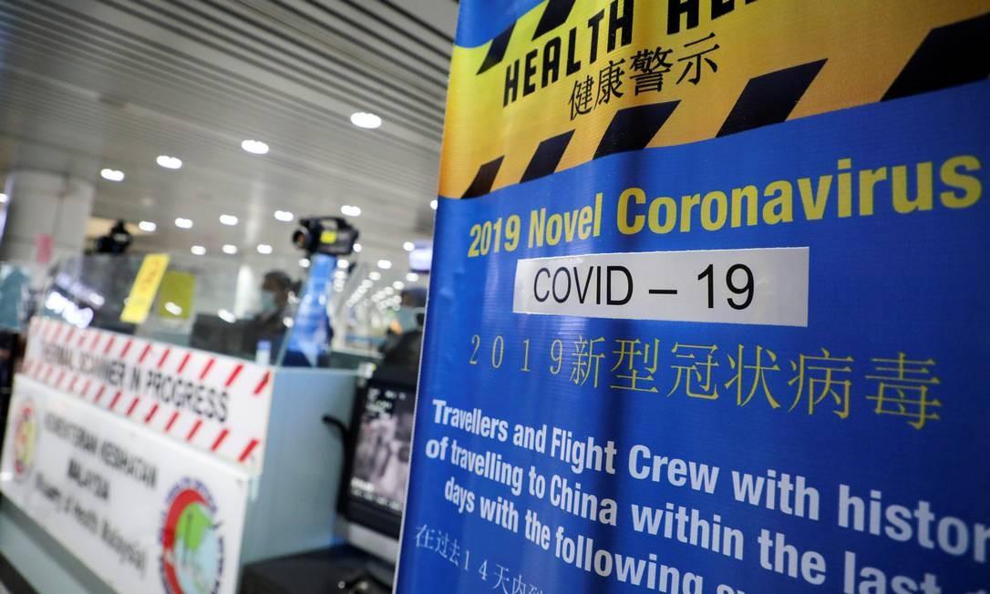 Banner sobre o Covid-19 é mostrado em um ponto de triagem térmica no terminal internacional de chegadas do Aeroporto Internacional de Kuala Lumpur em Sepang, Malásia Foto: LIM HUEY TENG / Reuters