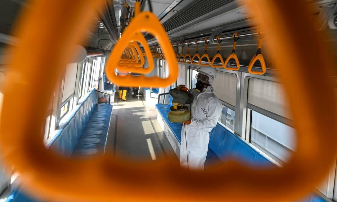 Funcionários em trajes de proteção pulverizam desinfetante no trem Light Rail Transit (LRT), em Palembang, Sumatra do Sul, depois que a Indonésia confirmou novos casos de doença Covid-19, a doença causada pelo coronavírus Foto: Antara Foto / Reuters