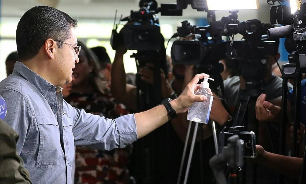 Presidente hondurenho, Juan Orlando Hernandez, oferece álcool em gel a jornalistas, durante coletiva, na qual confirmou os dois primeiros casos da Covid-19 no país Foto: HANDOUT / AFP