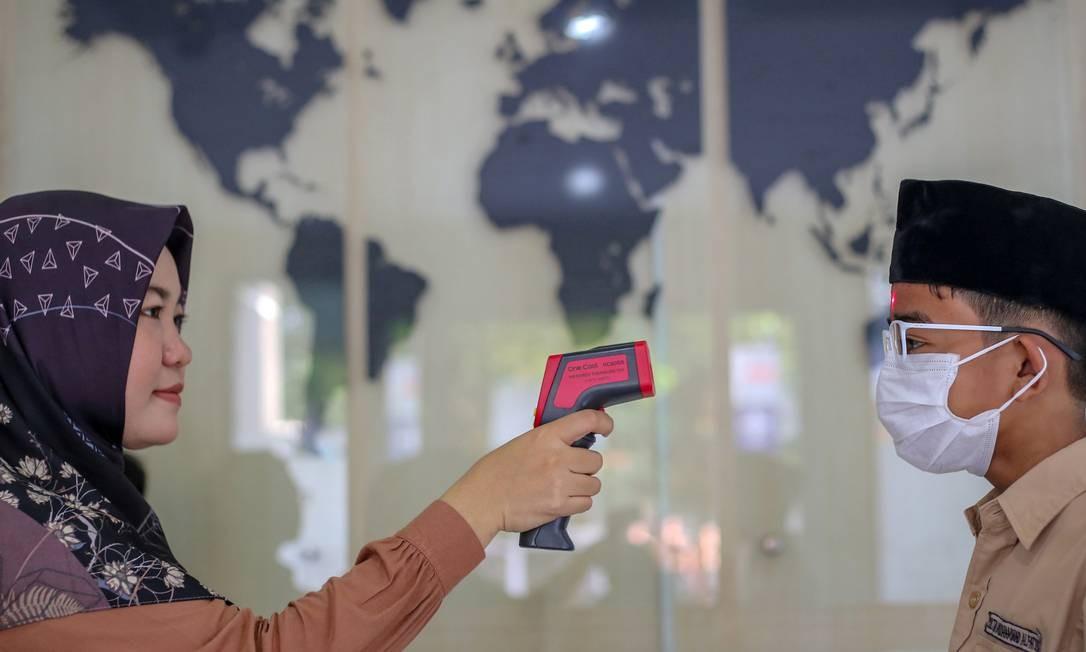 Professora verifica aluno com termômetro na escola em Jacarta, Indonésia Foto: Antara Foto / Reuters