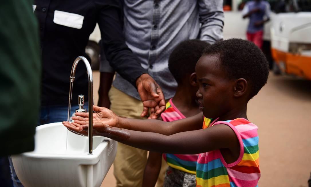 As irmãs gêmeas, Emeline e Eveline, lavam as mãos em uma estação pública de lavagem de mãos como medida preventiva contra o coronavírus no Nyabugogo Bus Park, em Kigali, Ruanda. O simples gesto é uma das maneiras mais eficientes de evitar o contágio Foto: MARGARET ANDRESEN / REUTERS
