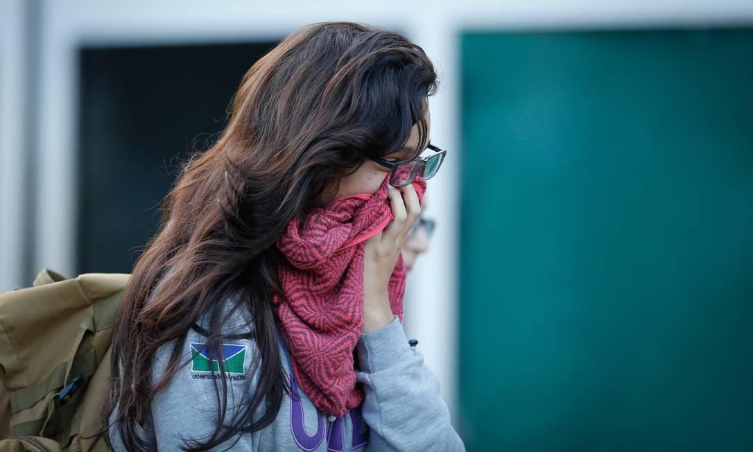 Jovem protege o rosto com lenço por medo de contágio no Hospital Regional da Asa Norte, em Brasília, onde há uma paciente internada com o coronavírus Foto: Pablo Jacob / Agência O Globo
