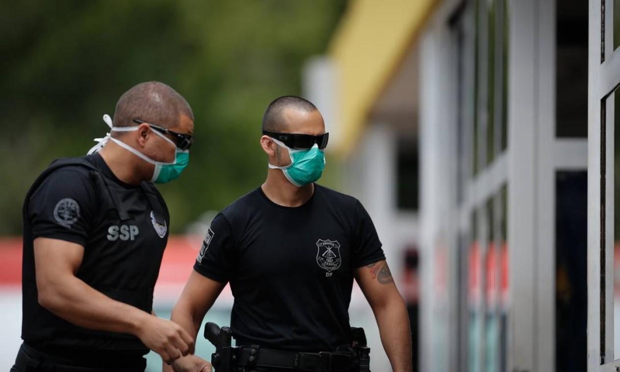 Policiais da Penitenciária do Distrito Federal (PDF) chegam ao Hospital Regional da Asa Norte, em Brasília, com máscara de proteção, em escolta de detento para atendimento médico Foto: Pablo Jacob / Agência O Globo
