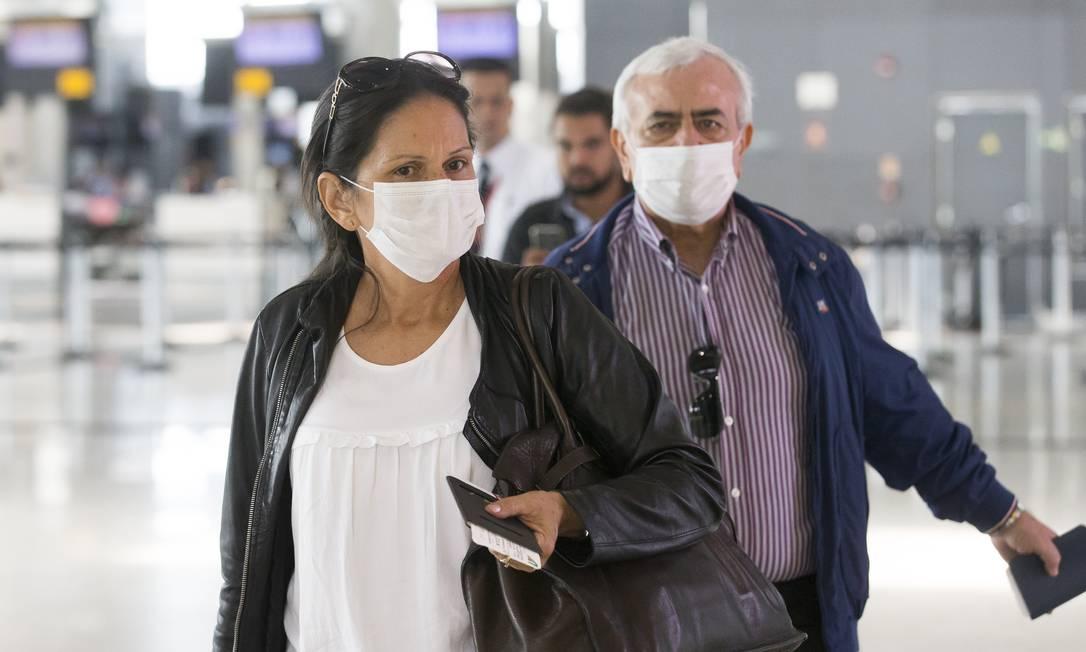 Lucelena Costa, de 52 anos, que mora há 20 anos na Itália e o italiano Troiano Enrico, de 65 anos embarcaram para a Europa, no Aeroporto Internacional de Guarulhos, usando máscara de proteção Foto: Edilson Dantas / Agência O Globo