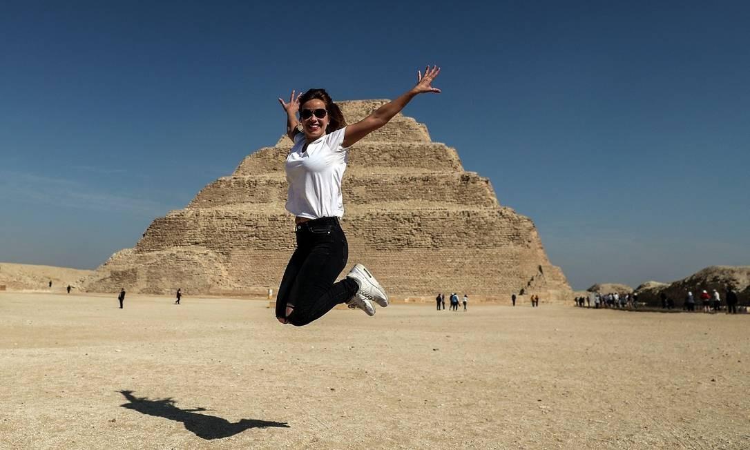 Turista salta para uma foto em frente à pirâmide de Djoser, a mais antiga do mundo, reaberta à visitação no Egito Foto: Mohamed el-Shahed / AFP