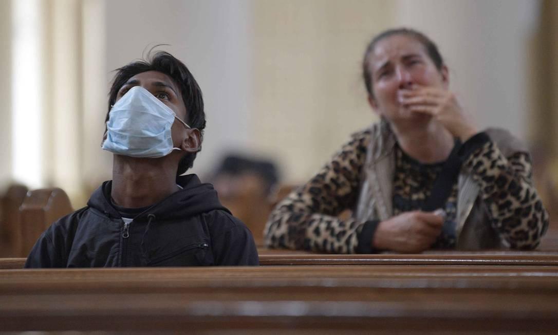 Homem usa máscara enquanto reza em igreja em Bogotá, na Colômbia Foto: RAUL ARBOLEDA / AFP