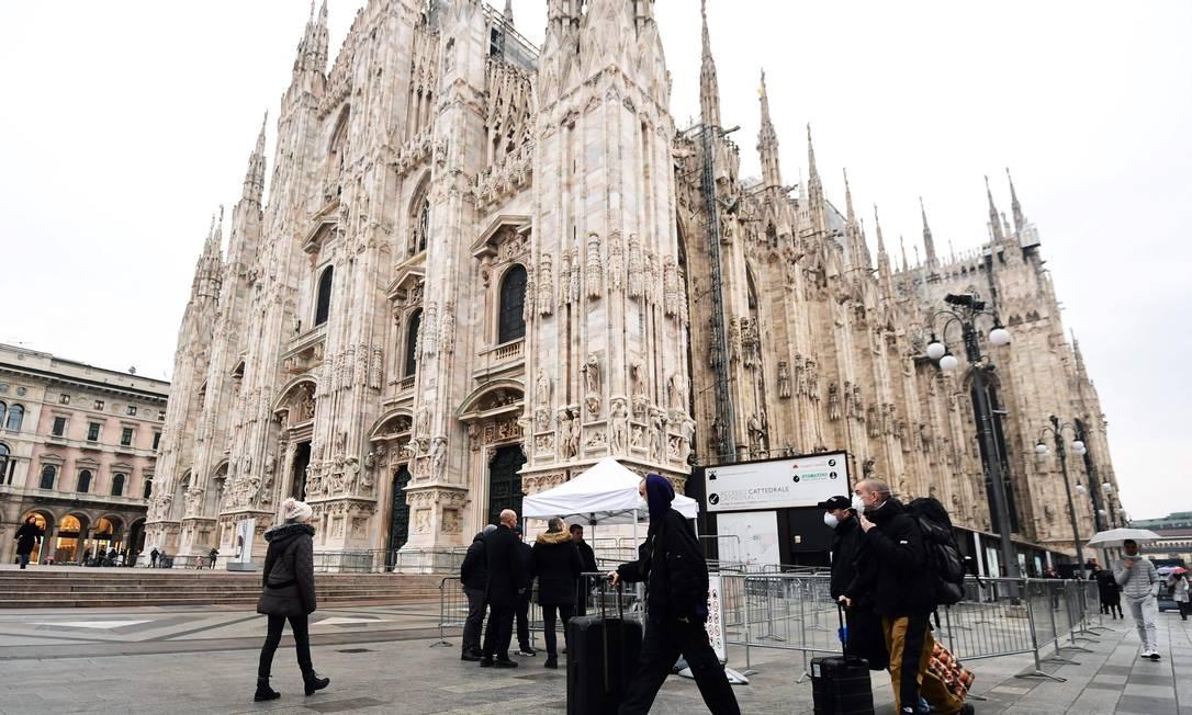 Turistas usando máscaras passam em frente à Catedral de Milão, na Lombardia, no dia 2 de março de 2020. Foto: Miguel Medina / AFP