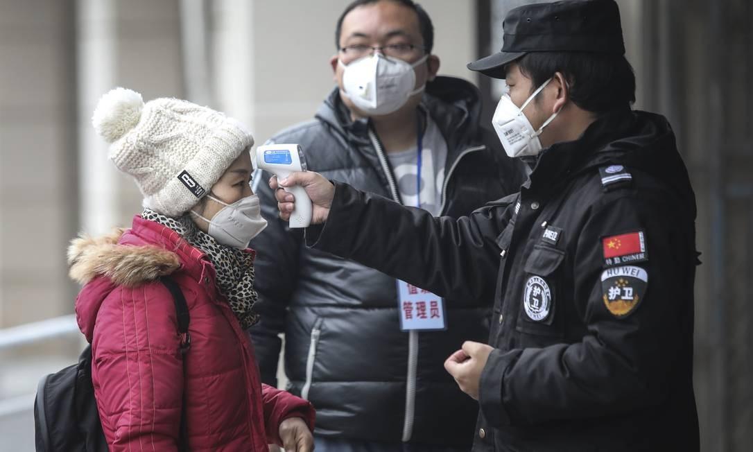 Seguranças realizam teste de temperatura em estações de trem, prédios residenciais e aeroportos Foto: Stringer / Getty Images