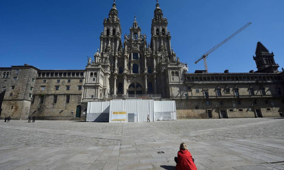 Mulher senta diante da catedral de Santiago de Compostela, em praça usualmente lotada, na Espanha Foto: MIGUEL RIOPA / AFP