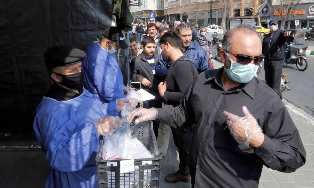 Pessoas na fila para receber um kit de precaução ao coronavírus fornecido pela Basij, uma milícia fiel ao estabelecimento da república islâmica do Irã, de um estande do lado de fora da estação de metrô Meydane Valiasr, na capital Teerã Foto: STRINGER / AFP