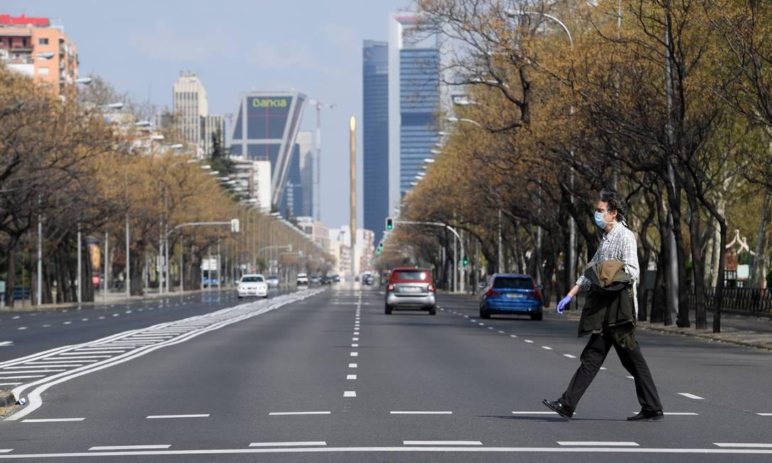 Homem de máscara e luvas atravessa a avenida La Castellana, em Madri, quase deserta Foto: Oscar del Pozo / AFP