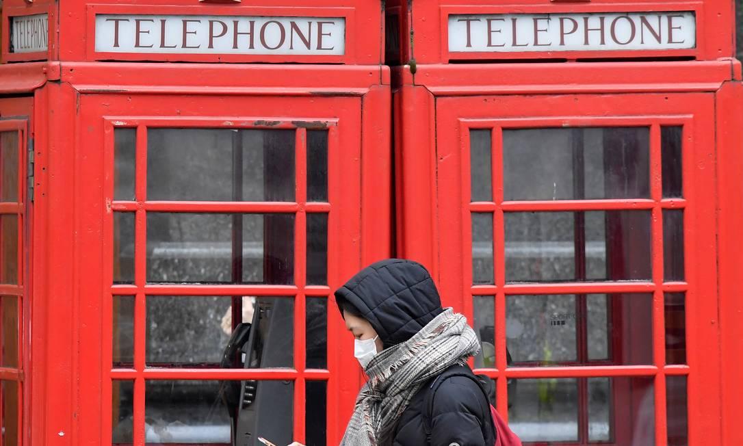 Mulher com máscara passa por cabines telefônicas em Londres Foto: TOBY MELVILLE / REUTERS