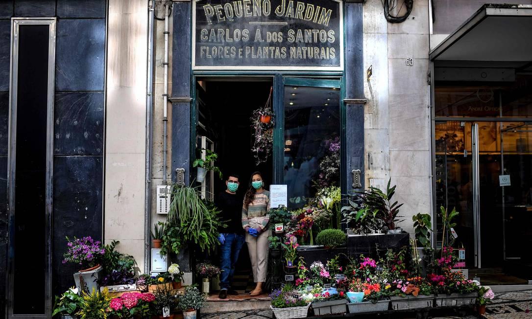 Floristas usam máscaras em Lisboa: pacientes infectados com coronavírus no país passaram de 169 a 245 de sábado para domingo, alta de 45% em 24 horas Foto: PATRICIA DE MELO MOREIRA / AFP