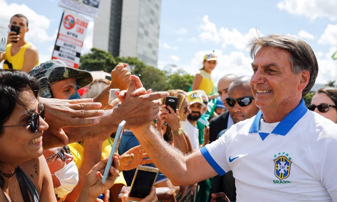 Presidente Jair Bolsonaro cumprimenta seus apoiadores durante manifestação em Brasília. Ele deveria estar em isolamento social por ter tido contato com pelo menos 10 membros de sua equipe Foto: SERGIO LIMA / AFP