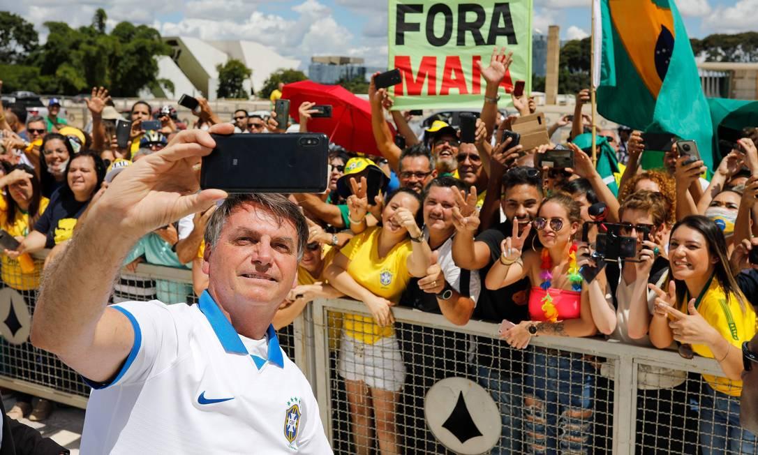 Presidente Jair Bolsonaro cumprimenta seus apoiadores durante manifestação em Brasília. Ele deveria estar em isolamento social por ter tido contato com pelo menos 10 membros de sua equipe. Compartilhar equipamentos, como celulares, também vai de encontro às recomendações por propiciar a contaminação Foto: SERGIO LIMA / AFP - 15/03/2020