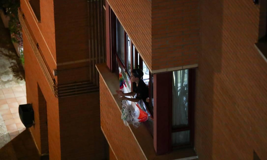 Em isolamento, em Madri, mulher aplaude pela janela. Evento foi organizado pelas redes sociais para mostrar gratidão aos trabalhadores da Saúde que atuam em meio à pandemia de coronavírus Foto: SERGIO PEREZ / REUTERS