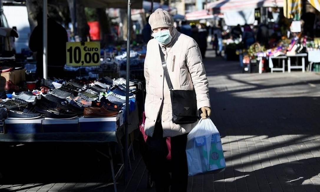 Imagem rara na Itália: mulher retorna do supermercado com máscara em ruas desertas de Milão Foto: Flavio Lo Scalzo/Reuters