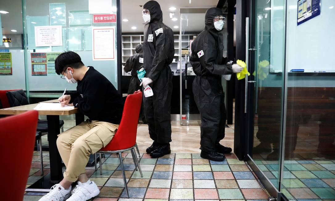 Soldados sul-coreanos limpam portas de escola com desinfetante Foto: KIM KYUNG-HOON/REUTERS