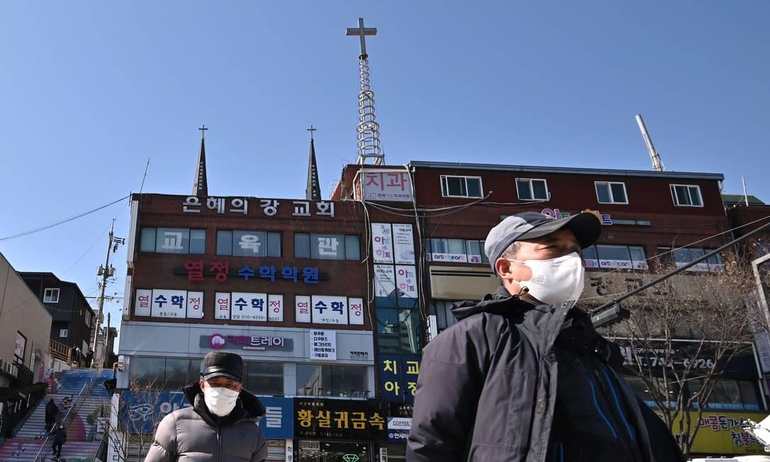 Pedestres caminham com máscaras de proteção em frente à igreja Grace River em Seongnam, na Coreia do Sul; templo foi fechado Foto: JUNG YEON-JE / AFP