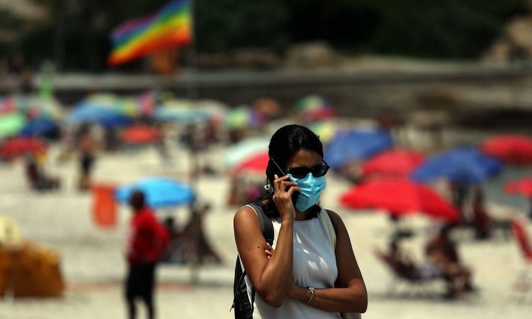 Uma mulher usa máscara enquanto fala ao telefone no calçadão do Arpoador, na Zona Sul do Rio Foto: Fabio Motta / Agência O Globo