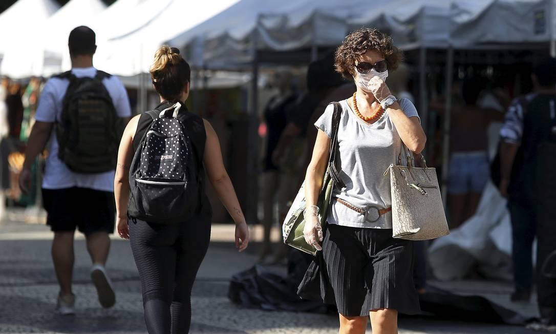 Mulher usa máscara e luvas enquanto caminha no Largo da Carioca Foto: Fabiano Rocha / Agência O Globo