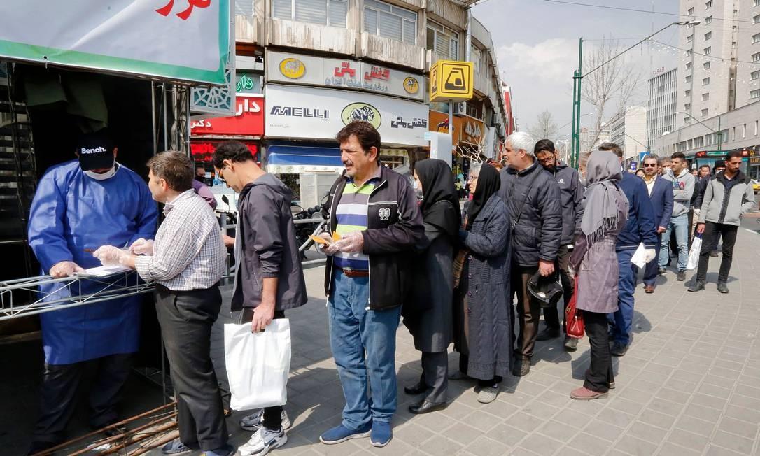 Pessoas fazem fila para receber pacotes com itens usados para tentar evitar o contágio pelo coronavírus em Teerã Foto: STRINGER / AFP