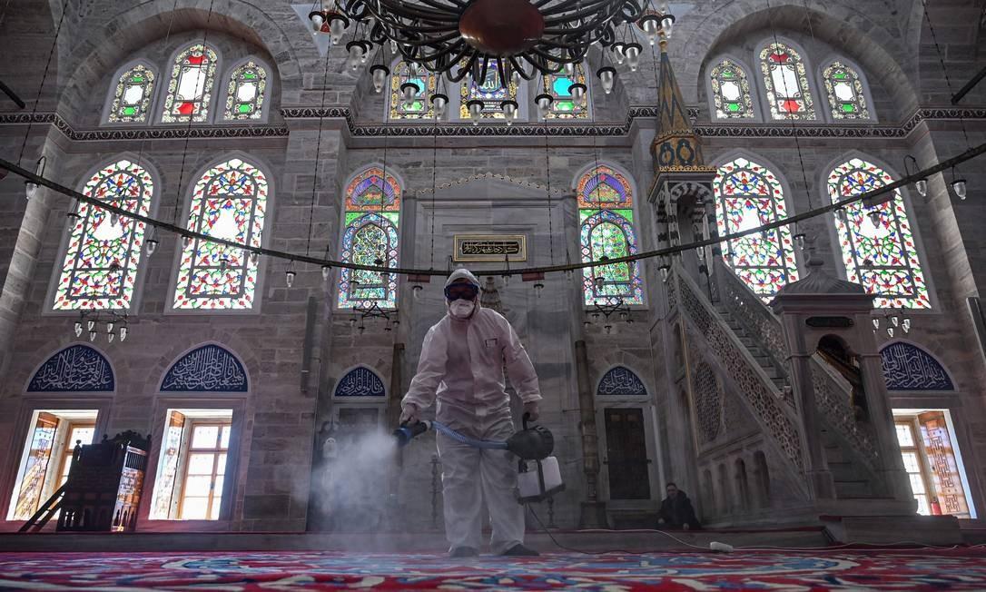 Funcionário da prefeitura de Istambul, na Turquia, desinfeta a mesquita Mihrimah Sultan como medida para evitar a expansão da Covid-19: país também está em alerta Foto: OZAN KOSE / AFP