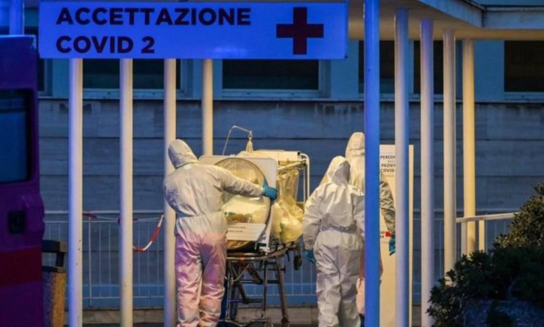 Em Roma, profissionais de saúde carregam paciente em tratamento intensivo para um hospital recém-construído destinado a pessoas com covid-19 Foto: ANDREAS SOLARO/AFP