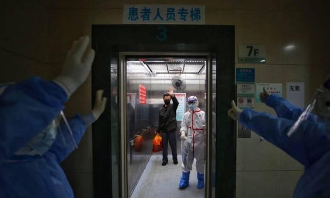 Equipe de hospital em Wuhan, na China, se despede de paciente dispensado após se recuperar da Covid-19 Foto: AFP