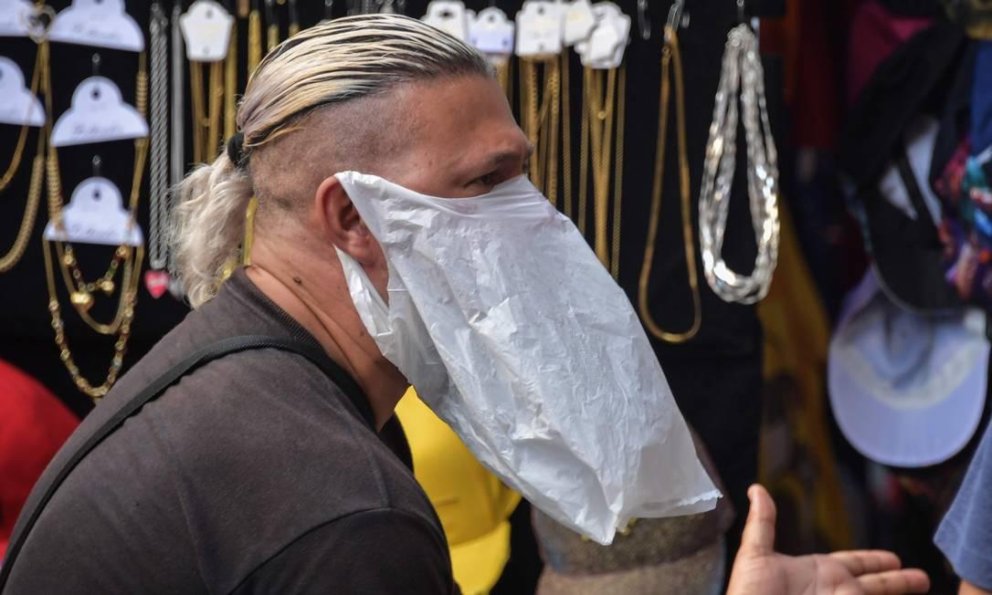 Vendedor de rua usa sacola plástica como medida preventiva contra a disseminação do novo coronavírus, no centro de São Paulo Foto: Nelson Almeida / AFP