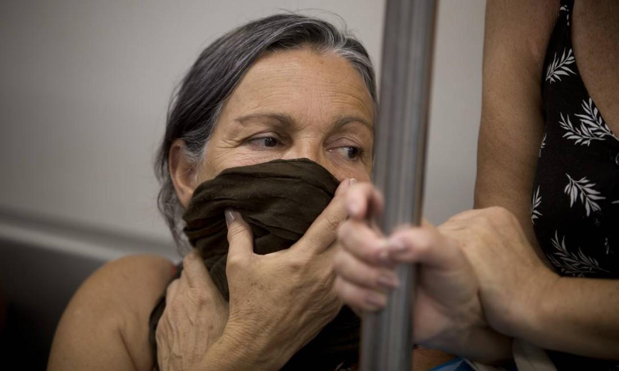Mulher coloca um lenço na boca durante viagem de metrô no Rio Foto: Márcia Foletto / Agência O Globo