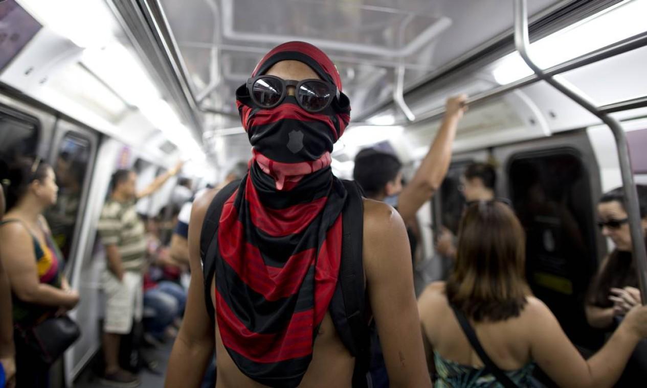 Sem conseguir encontrar material para se proteger contra o novo coronavírus, cariocas improvisam como podem. No metrô do Rio, jovem usa a camisa para tentar se proteger do COVID-19 Foto: Márcia Foletto / Agência O Globo