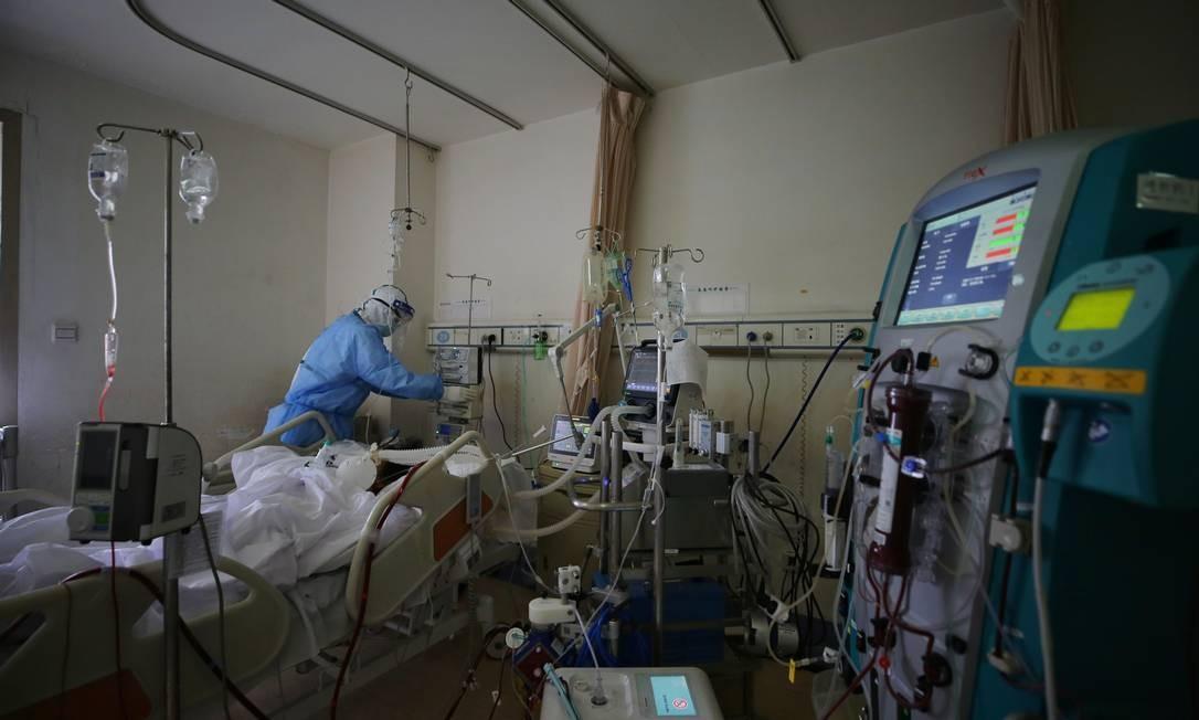 Médico usa proteção para atender paciente com Covid-19 em hospital na China Foto: STR / AFP