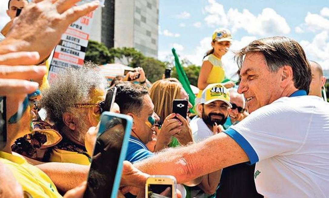 Bolsonaro cumprimenta apoiadores em manifestação, domingo: presidente quebrou protocolos da OMS e se expôs ao contágio por coronavírus Foto: SERGIO LIMA/AFP/15-3-2019