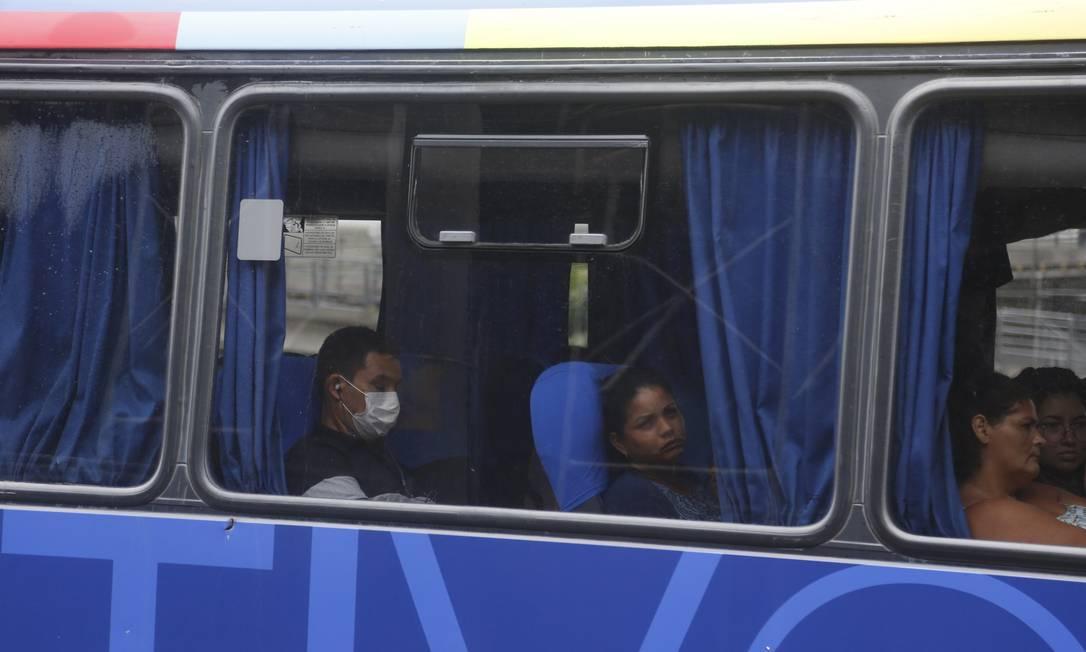 Rapaz usa máscara dentro de um ônibus no Rio Foto: Fabiano Rocha / O Globo