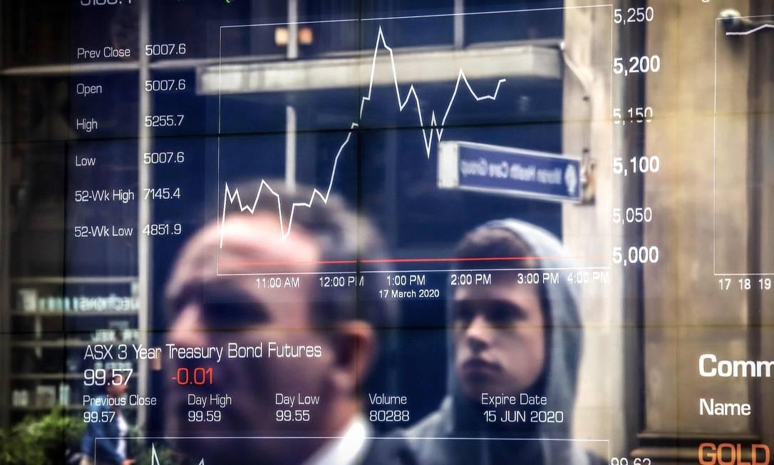 Pessoas observam o gráfico de variação da Bolsa de Valores Foto: DAVID GRAY/AFP/17-03-2020