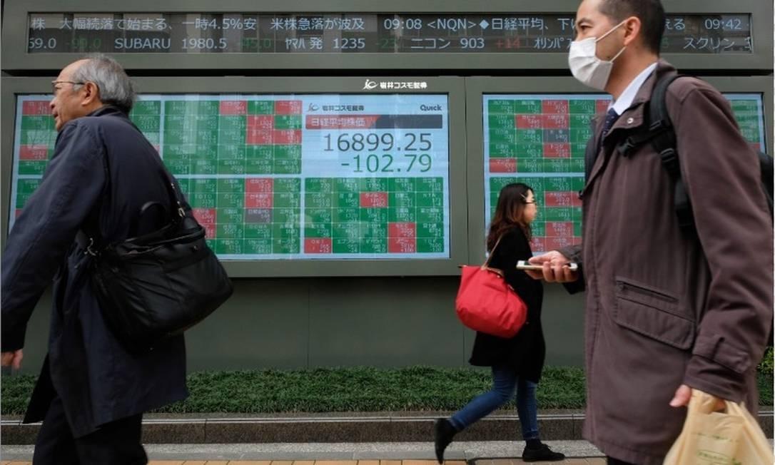 Pedestres passam em frente a um painel com as cotações da Bolsa de Tóquio Foto: AFP