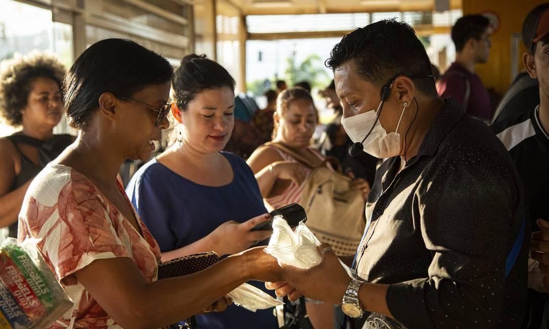 Ambulante vende álcool gel e máscaras de proteção na estação Mato Alto, em Guaratiba Foto: Hermes de Paula / Agência O Globo