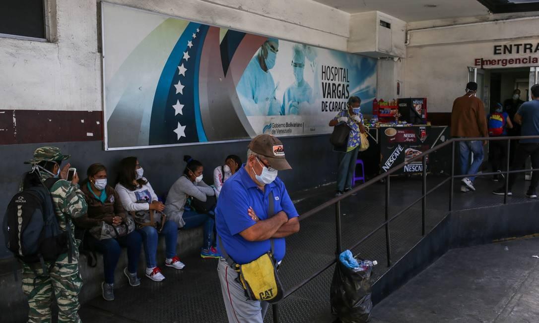 Pacientes com máscara esperam do lado de fora do Hospital Vargas, em Caracas Foto: CRISTIAN HERNANDEZ / AFP