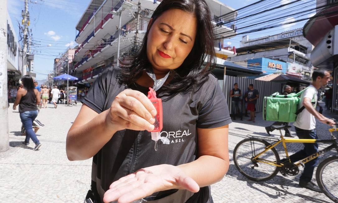 A vendeddora Michelle Santiago com o álcool em gel que sua empresa forneceu Foto: Cléber Júnior / O Globo