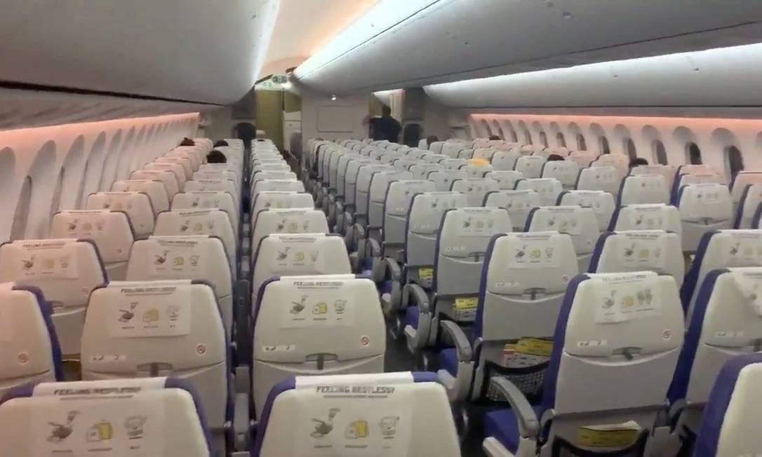 Cabine de um avião praticamente sem passageiros num voo de Cingapura para Bangcoc Foto: Samuel Horstead / Via Reuters
