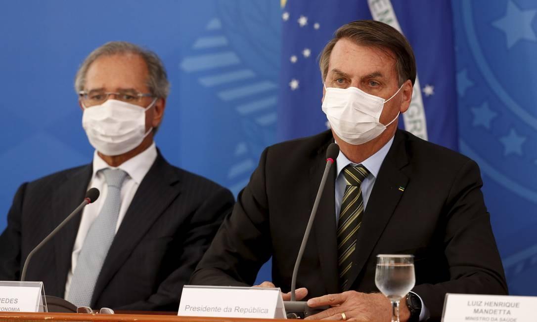 Na coletiva com o presidente Jair Bolsonaro e o ministro Paulo Guedes, todos usaram máscaras: anúncio de vouchers a informais Foto: Pablo Jacob