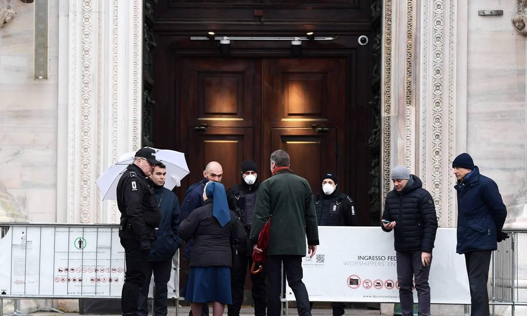 Agentes de segurança com máscaras controlam entrada de pessoas na catedral de Milão no começo de março Foto: MIGUEL MEDINA / AFP